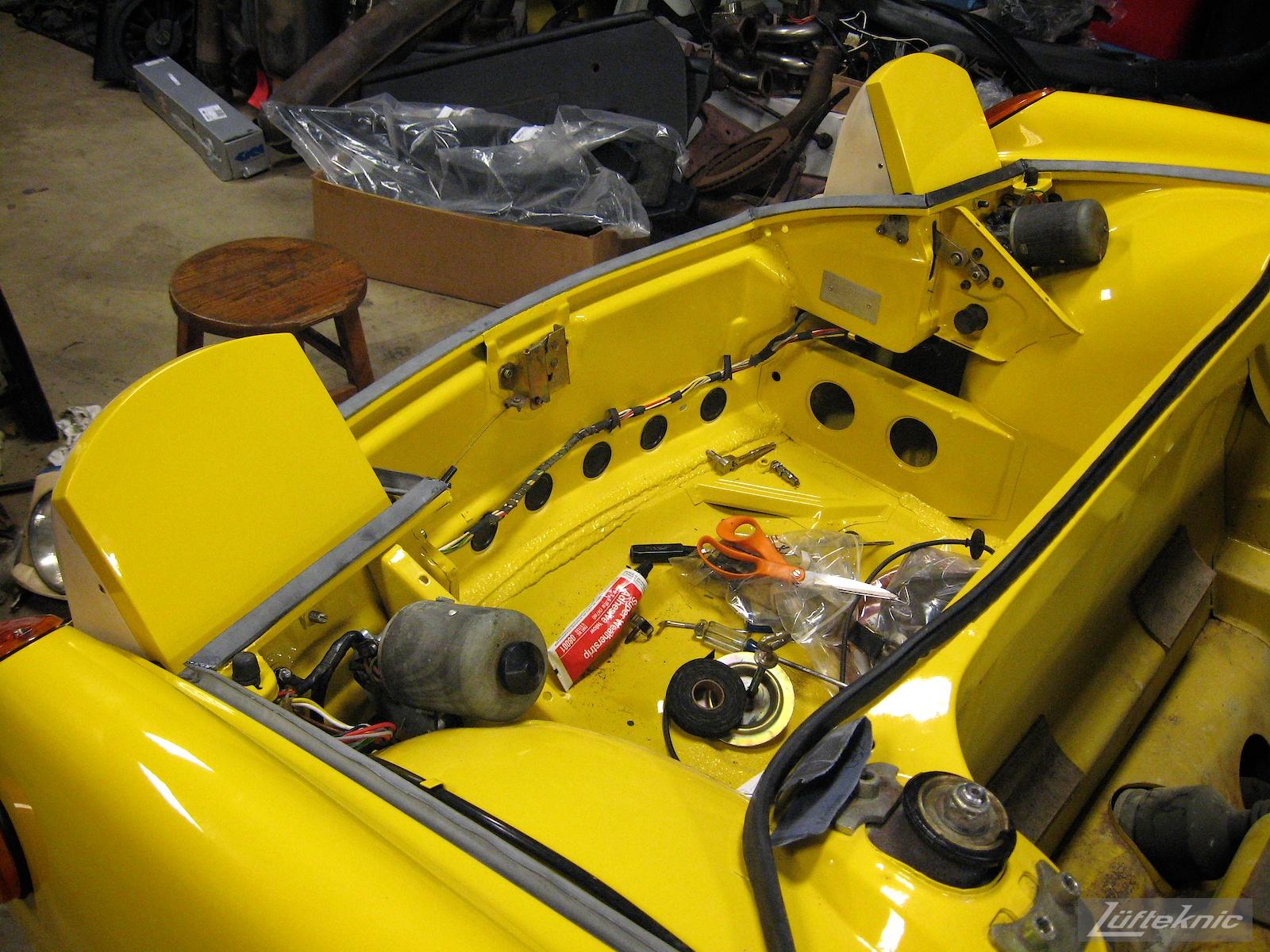 Reassembling headlights and lighting on a restored yellow Porsche 914 at Lufteknic.
