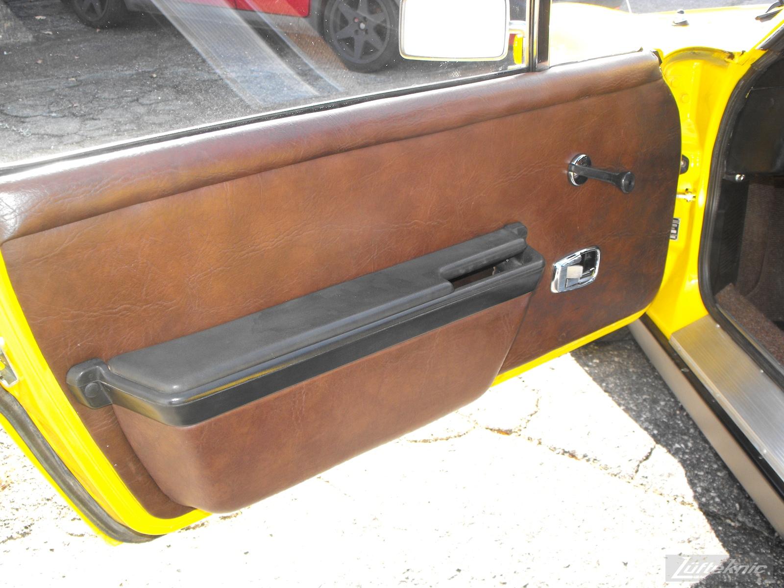 Original brown door panels on a completely restored yellow Porsche 914 posing in the parking lot of Lufteknic.