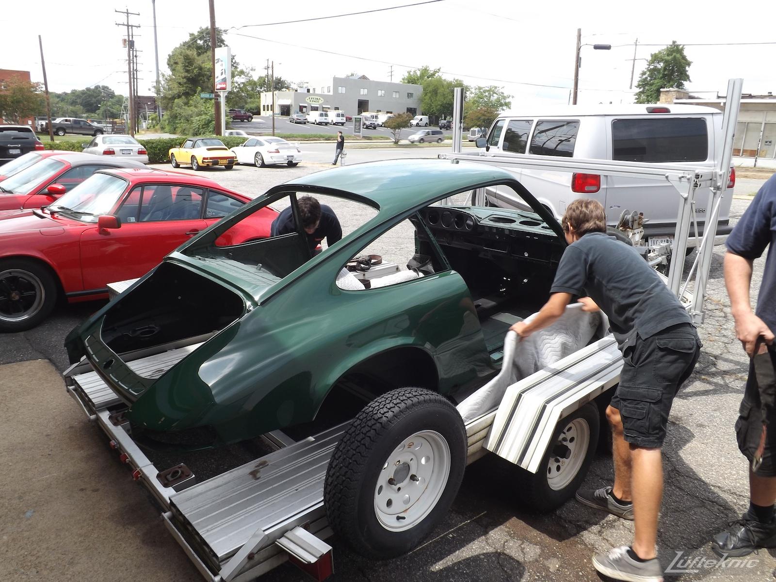 Unloading the freshly painted body shell of an Irish Green Porsche 912 undergoing restoration at Lufteknic.