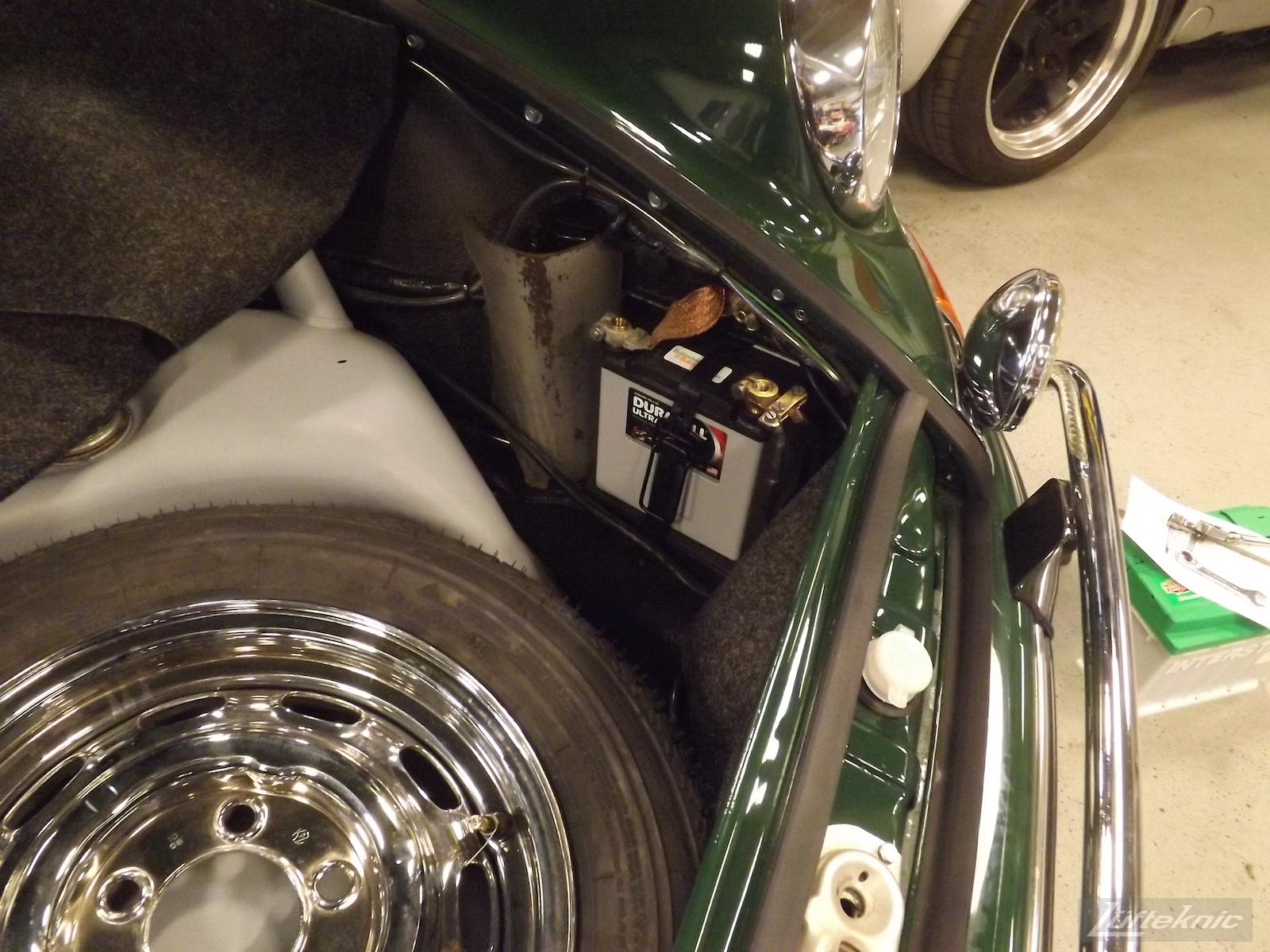 Newly installed battery and lights under the hood of an Irish Green Porsche 912 undergoing restoration at Lufteknic.