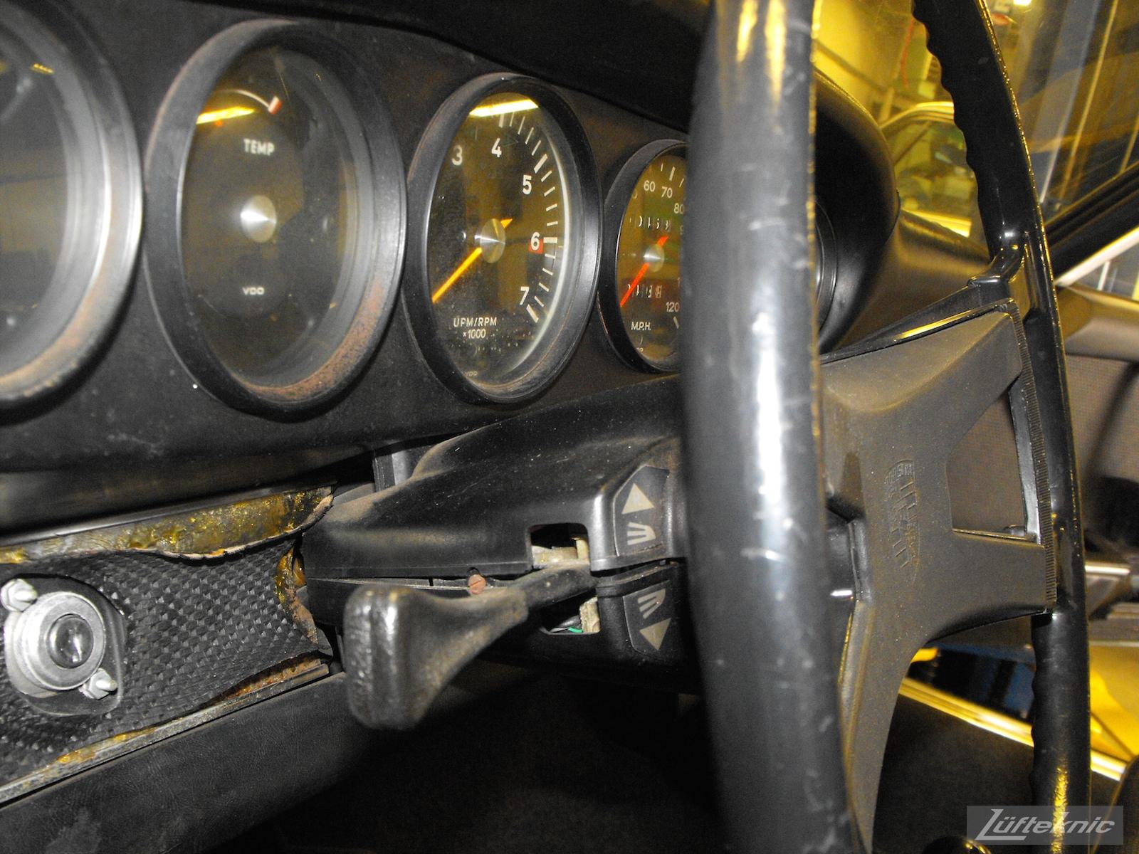 Worn dash and gauge components shown of an Irish Green Porsche 912 undergoing restoration at Lufteknic.