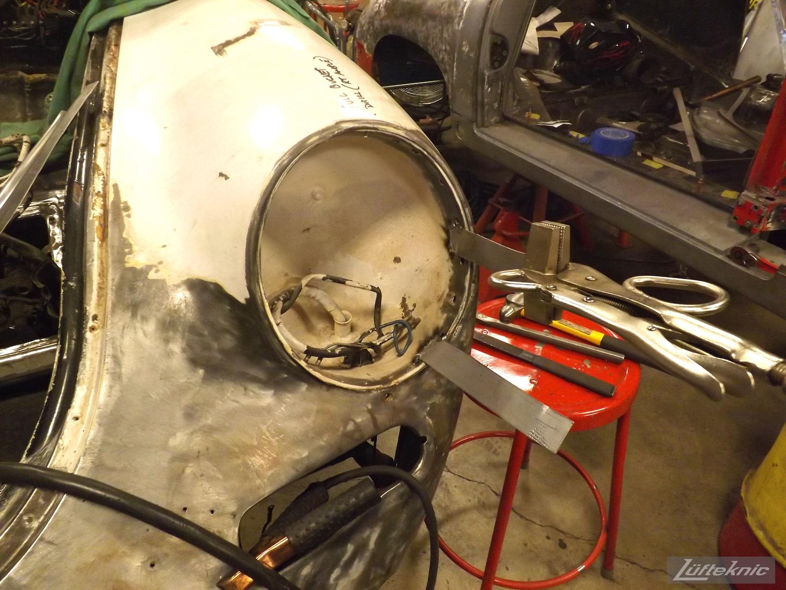 Headlight bucket adjustment on a White 1964 Porsche 356SC being restored.