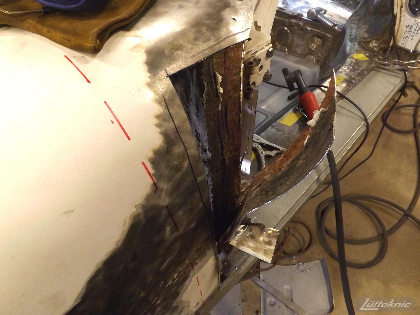 Rust under body panel on a White 1964 Porsche 356SC being restored.