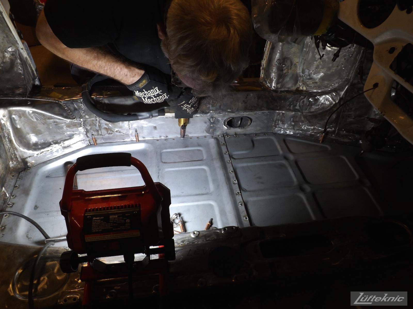 Spot welding the floor of a White 1964 Porsche 356SC being restored.